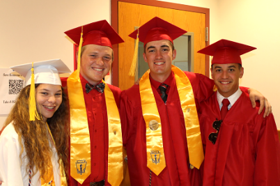 three male and one female graduates posing indoors in cap and gowns