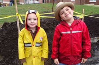 two elementary students standing in front of a groundbreaking ceremony